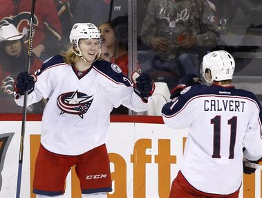 Columbus Blue Jackets' William Karlsson, left, from Sweden, celebrates with teammate Matt Calvert after scoring the game winning goal against the Calgary Flames during third period NHL action in Calgary, Alta., Friday, Feb. 5, 2016. THE CANADIAN PRESS/Larry MacDougal