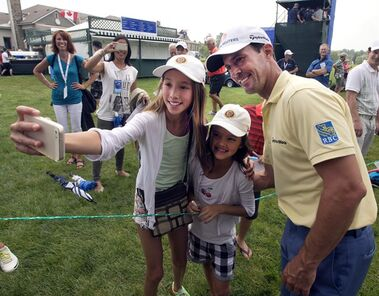 Canada's Mike Weir, from Brights Grove, Ont., poses for a selfie with Kaylee Chin, left, and Maya Cunningham, center, during the Pro-Am event at the Canadian Open golf championship Wednesday, July 23, 2014 at Royal Montreal golf club in Montreal. THE CANADIAN PRESS/Ryan Remiorz