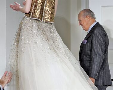 FILE - In this Feb. 4, 2008, file photo, designer Oscar de la Renta is applauded after the presentation of his fall 2008 collection during Fashion Week in New York. The designer, who died Monday, Oct. 20, 2014, at 82, shaped American couture half a century ago when it emerged as a serious rival to European fashion designers. (AP Photo/Richard Drew, File)
