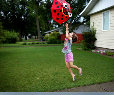 Eight-year-old Claira Stitt plays with an umbrella in the front yard of her home on 28th Street as showers subside on Thursday.