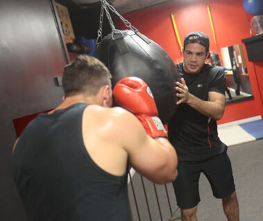 Rodman Batson works with one of his boxers at Peak Performance Gym on Thursday ahead of a bout on Saturday.