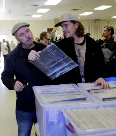 Jordan Morris shows his dad, James Morris, his latest find at Brandon's Biggest Record and Music Sale at the Royal Canadian Legion Branch No. 3 on Sunday.