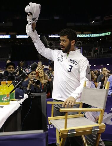 Seattle Seahawks' Russell Wilson acknowledges the crowd as he arrives for media day for NFL Super Bowl XLIX football game Tuesday, Jan. 27, 2015, in Phoenix. (AP Photo/Mark Humphrey)