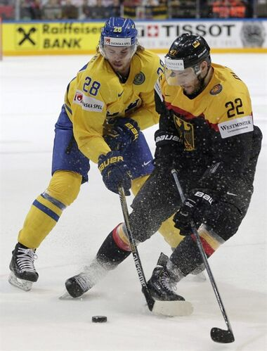 Sweden's Elias Lindholm, left, challenges Germany's Matthias Plachta, right, during the Hockey World Championships Group A match in Prague, Czech Republic, on May 7, 2015. THE CANADIAN PRESS/AP, Petr David Josek