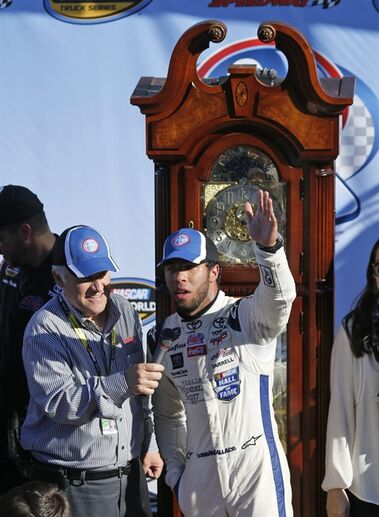 Darrell Wallace Jr., celebrates winning the NASCAR Truck Series auto race in victory lane with the grandfather clock trophy at Martinsville Speedway in Martinsville, Va., Saturday, Oct. 25, 2014. (AP Photo/Steve Helber)