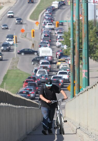 Chris Prince walks his bicycle up the Daly Overpass as the northbound lanes of 18th Street are immobilized by traffic backed up by roadwork, Wednesday afternoon.