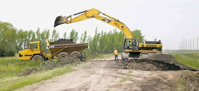 A crew builds up the east side of the Portage Diversion on Saturday. The province says it's prepared to cut the nearby Hoop and Holler dikeon the Assiniboine River again as a last resort to avoid an uncontrollable breach elsewhere.