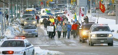 PHIL HOSSACK / WINNIPEG FREE PRESSYoung people from Kinonjeoshtegon First Nation march down Memorial Boulevard to the legislature Monday to protest the federal Bill C-45.