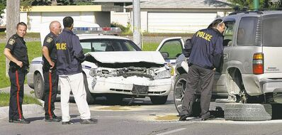 KEN GIGLIOTTI / WINNIPEG FREE PRESS ArchivesWinnipeg officers examine the July 2007 scene involving a crash between a police cruiser and an SUV at the corner of Grant Avenue and Lindsay Street.