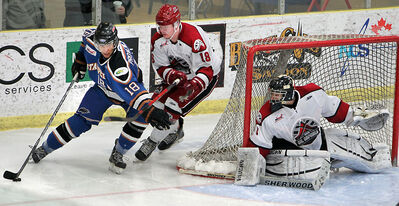 Virden Oil Capitals defenceman Cole Hamblin and goalie Adam Iwan watch Swan Valley Stampeders' Max Provencher swoops around the net in MJHL action on March 8.