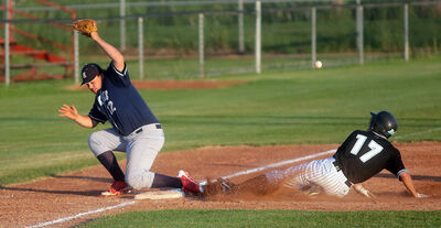 Ryan Duncan of the Brandon Marlins slides into third base as a wild throw sails past Reston's Zane Sawyer during Sunday night's Manitoba Senior Baseball League playoff game at Andrews Field. The Marlins won 5-0 to sweep the best-of-five semifinal series.