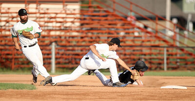 Brandon Marlins baserunner Ty Webber gets caught in a run-down between Casey Clark (left) and Zach Steckler of the Brandon Cloverleafs during Game 3 of the Manitoba Senior Baseball League final at Andrews Field on Sunday night. The Cloverleafs won 3-2 in 12 innings.