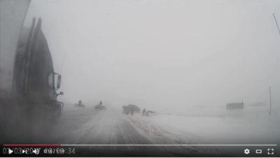 In this still image captured from a video by NZP Chasers, a semi-trailer can be seen approaching a snowmobile rider on the Trans-Canada Highway. The semi struck and injured the snowmobiler, but the rider is reportedly doing OK. Police and a witness say that the highway was closed during Tuesday's blizzard, and the snowmobile rider had been helping stranded motorists west of the city.