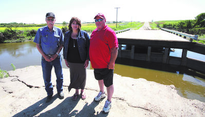 RM of Edward Reeve Ralph Wang and Councillors Debbie McMechan and Carey Murray stand in front of infrastructure that was devastated by the floods from summer rains.