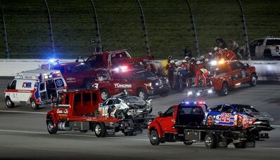 The cars of Danica Patrick (10) and Joey Logano (22) are hauled past rescue efforts for Aric Almirola, back, during the NASCAR Monster Cup auto race at Kansas Speedway in Kansas City, Kan., Saturday, May 13, 2017. (AP Photo/Colin E. Braley)