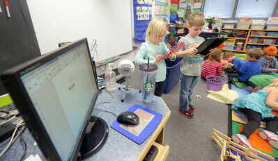 Oak Lake Community School junior kindergarten students Micah Thiessen, right, and Courtney Cochrane use their school's iPads to record images of their class at play on Tuesday afternoon.