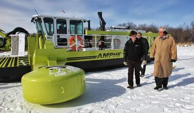 Photos by Mike Deal / Winnipeg Free Press Premier Greg Selinger (right) inspects one of the Amphibex units with St. Andrews Reeve Don Forfar on Wednesday as the machines begin their work (bottom).