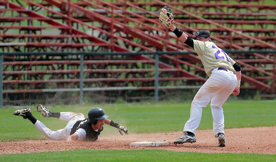 Vincent Massey Vikings' Clark Whelpton raises his glove after tagging out Kenton Scott of the Otter Nelson River Nikiks at third base on a steal attempt during the provincial high school baseball championship on Thursday at Andrews Field.