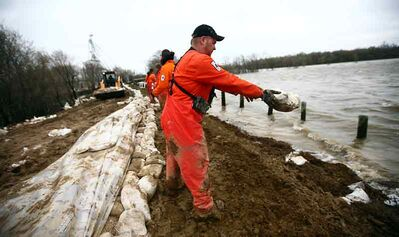 In this May 2011 photo, firefighters with Manitoba Conservation pile sandbags in an effort to top up the southern dike near the Co-op Feed elevator in Brandon.