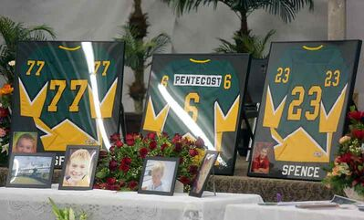 The hockey sweaters of Logan Spence, Dawson Pentecost and Gage Spence are displayed along with photos and flowers at the front of the funeral service for the three young boys and Darren Spence, Logan and Gage's father, in Waskada, on Monday.