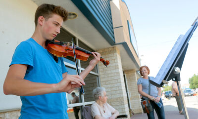 Suzuki violin student Owen Chambers performs on the streets of Carberry during Saturday's heritage festival. Chambers was delighted to have his mother Kim Chambers and grandmother Jess Clark as spectators.