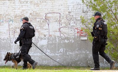 Brandon Police Service members search for a suspect behind The Brandon Sun's building on Rosser Avenue after a chase on Thursday afternoon.