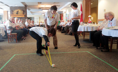 Victoria Landing health and wellness director Claudia Nohr measures a shot during the bocce ball tournament on Wednesday.