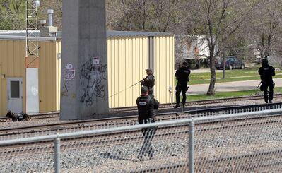 Members of Brandon Police Service's Tactical Response Unit, Canine Unit and other members search for a suspect along the CP tracks under the Eighth Street bridge after a chase on Thursday afternoon.