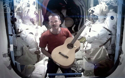 "Canadian astronaut and ISS commander Chris Hadfield is framed by spacesuits as he performs David Bowie's ""Space Oddity"" during his stint last year as commander of the International Space Station. This Monday, he will again be front and centre in the music world when the song I.S.S (""Is Somebody Singing""), which Hatfield co-wrote with Ed Robertson of the Barenaked Ladies, is broadcast countrywide during Music Monday celebrations."
