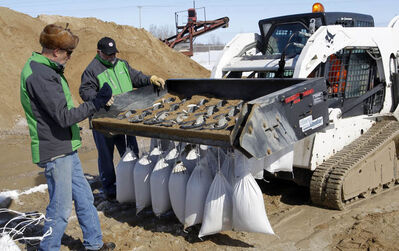 Jim Stinson, the Canadian distributor for Sand Masters gives a demonstration of the Sand Masters 20 sand bagging machine to officials in the rural Municipality of Springfield.