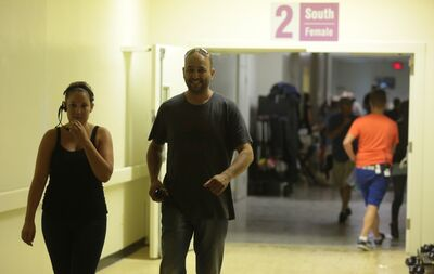 Alyssa Robbins, locations assistant, walks down the hallway's with Neal Baksh, production assistant with locations, between scene shoots at Assiniboine Community College's North Hill campus on Friday.