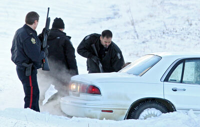 With guns drawn, Brandon Police Service members take down a suspect in a string of car robberies after a stolen Buick LeSabre hit the ditch on Highway 110 east of Brandon after a police pursuit on Thursday morning. Two suspects, a man and a woman, were taken into custody.