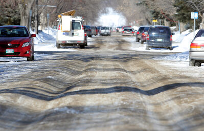 A car makes it along 16th Street on Wednesday. Snow buildup on 16th Street had created deep ruts. Snow removal crews have since plowed the street.