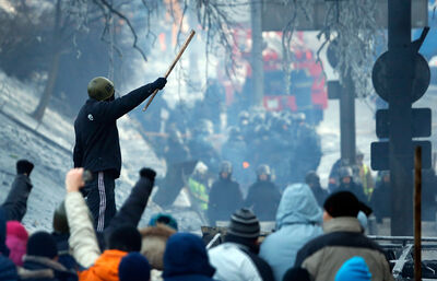 Protesters stand behind a barricade in front of riot police in central Kyiv, Ukraine, on Sunday. Ukraine's opposition called off a massive rally planned for Sunday because of the funeral for a protester killed in clashes with police last week.