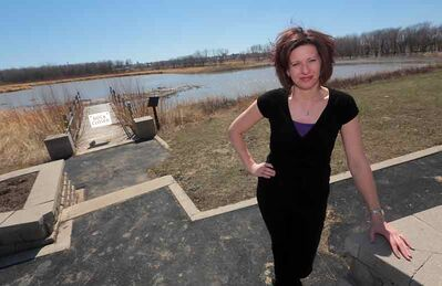 Lois MacDonald, Riverbank Development & Tourism Services manager, stands on the boardwalk as the Assiniboine River spills into the west pond at the Discovery Centre.