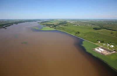 The swollen Assiniboine River covers farmland along Grand Valley Road west of Brandon, Man. as seen from the air on Sunday, July 6, 2014. THE CANADIAN PRESS/Tim Smith
