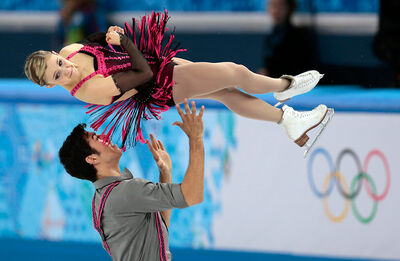 Rudi Swiegers tosses Paige Lawrence in the air during the Virden pairs skaters' short program on Tuesday in Sochi.