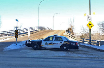 A patrol car blocks the south entrance to the Eighth Street Bridge after a vehicle struck the bridge on Tuesday, causing structural concerns.