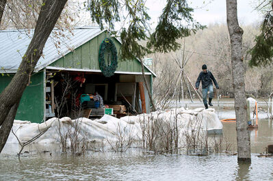 In this May 11, 2011, photo, Dave Barnes checks the water pumps at his garage at his flooded Brandon property as the swollen Assiniboine River threatens his home.