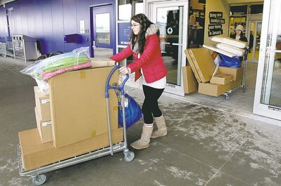 Terri Seguin (left) and Kristy Lanauze take their flat-packed furniture out after the grand opening.