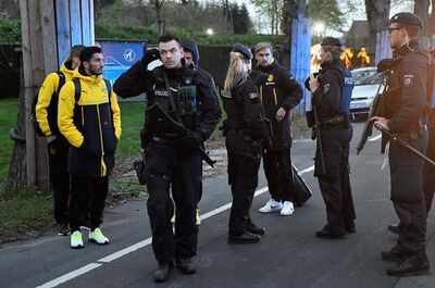 FILE - In this April 11, 2017 file photo Dortmund's Marcel Schmelzer, third from right, talks to police officers outside the team bus after it was damaged in an explosion before the Champions League quarterfinal soccer match between Borussia Dortmund and AS Monaco in Dortmund, western Germany. (AP Photo/Martin Meissner, file)