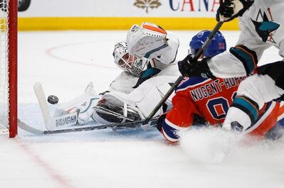San Jose Sharks goalie Martin Jones, left, dives for the puck as Edmonton Oilers' Ryan Nugent-Hopkins crashes into him during overtime NHL hockey round one playoff action in Edmonton, Thursday, April 20, 2017. THE CANADIAN PRESS/Jeff McIntosh