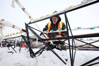 Wayne Isleifson with the City of Brandon disassembles one of the Waterfall of Lights displays at the skating oval to move it away from floodwaters from the Assiniboine River on Wednesday afternoon. The displays will be set up on the south side of the road.