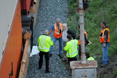 Brandon Police Service members and Canadian Pacific railway workers and a medical examiner talk at the scene of a fatal incident involving a CP train at the rail-yards just east of the First Street Bridge in Brandon in 2012. A sheet covering a body is seen in the background.