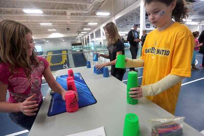 Halylie Bryant, left, Kylie Black and Alex Smale race against the clock in a speed cup-stacking competition at the Brandon University Healthy Living Centre during Saturday's open house.
