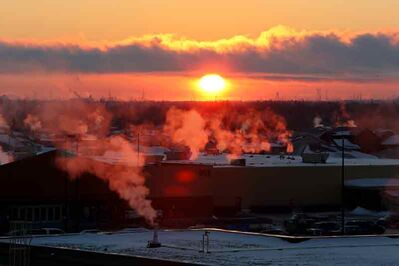 Steam from the chimneys of businesses and homes adjacent to the North Hill is illuminated by the rising sun on a cold Tuesday morning.