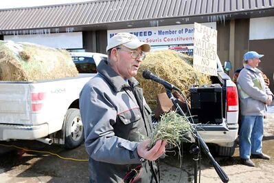 Fred Tait, a farmer from Rossendale, holds up some alfalfa while speaking during a protest rally opposing the introduction of genetically modified alfalfa in front of Brandon-Souris Conservative MP Merv Tweed's constituency office on 18th Street North on Tuesday afternoon.
