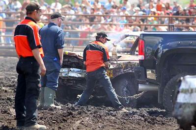Crews work to remove bent wrecks during the Demolition Derby as the Summer Fair wrapped up Sunday.