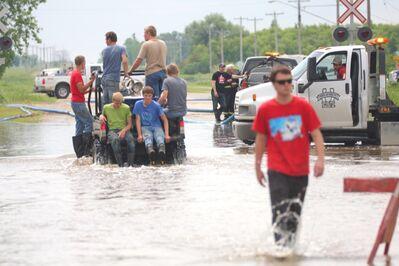Reston residents make their way through some of the deepest parts of a flood on Saturday afternoon. Reston saw flood waters as high as four feet after it was hit with between six and eight inches of rain on Friday night, affecting around 400 of the town's residents.
