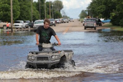 A young man drives a quad along a flooded street in the community of Reston while helping in the flood relief efforts on Wednesday.